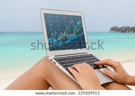 Woman working on a computer at the beach. Sandy beach and forex screen. A concept of the freelance.  - stock photo