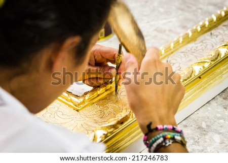 Woman working on a picture frame in her workshop - stock photo