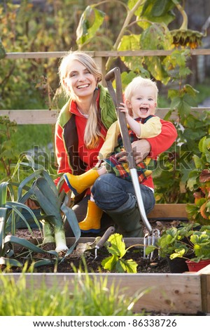 Woman working on allotment with child - stock photo