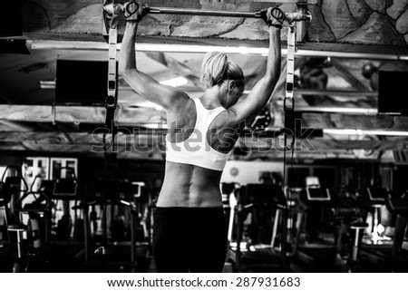 Woman working out back exercises. pull ups. - stock photo