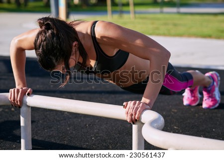 woman working out in gym doing pushups on equipment outdoors having fun - stock photo