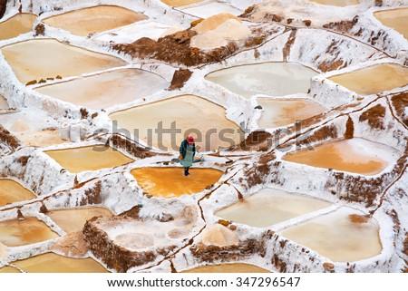 Woman working the salt evaporation ponds in Maras, Peru - stock photo