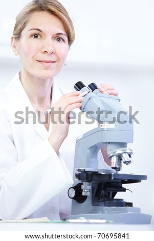 Woman working with a microscope in lab - stock photo