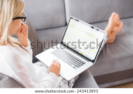 Woman working with computer while sitting on couch - stock photo