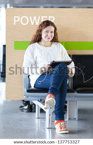 Woman working with electronic devices in place to charge - stock photo