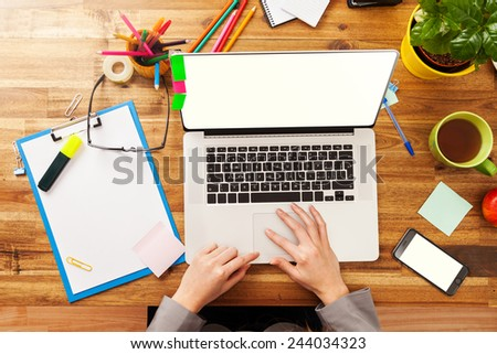 Woman working with laptop placed on wooden desk. Shot from aerial view - stock photo