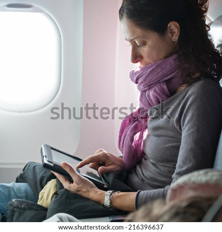 Woman working with tablet inside airplane. - stock photo