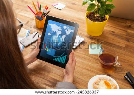 Woman working with tablet placed on wooden desk with digital scheme. Shot from aerial view - stock photo