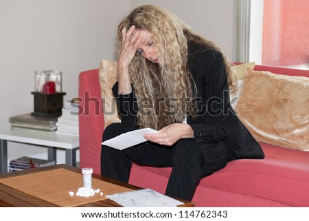 woman worried about bills and debt and foreclosure and thinking about taking pills - stock photo