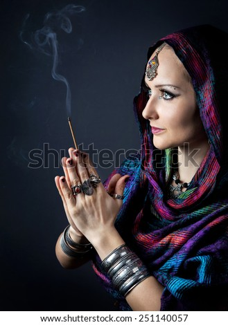 Woman wrapped in scarf holding incense stick in hands with Namaste gesture at dark background  - stock photo