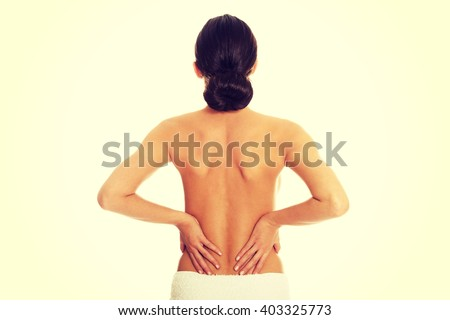 Woman wrapped in towel having back pain - stock photo