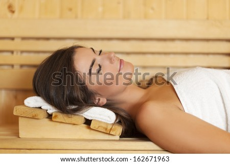 Woman wrapped in white towel laying in sauna  - stock photo