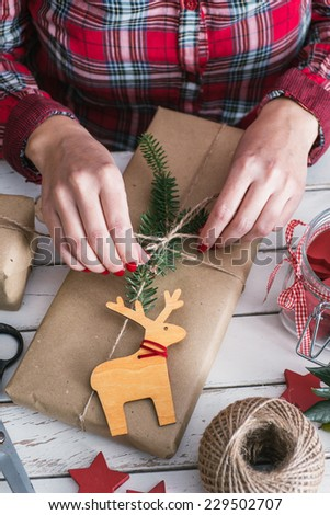 Woman wrapping cool christmas gift - stock photo