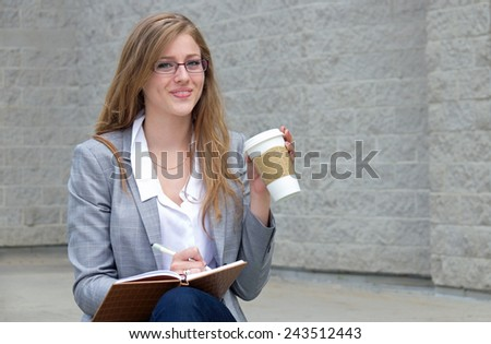 Woman writes in journal and drinks her coffee - stock photo