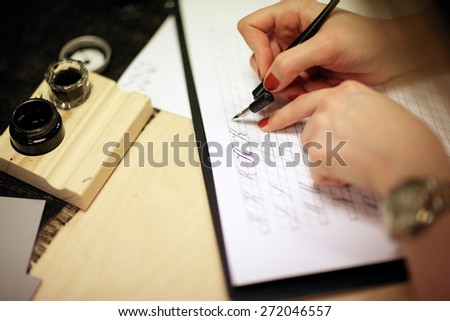 Woman writing calligraphic letters - stock photo