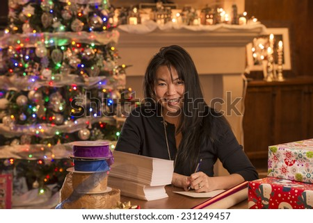 woman writing cards / looks like they are for christmas / judging by decor - stock photo