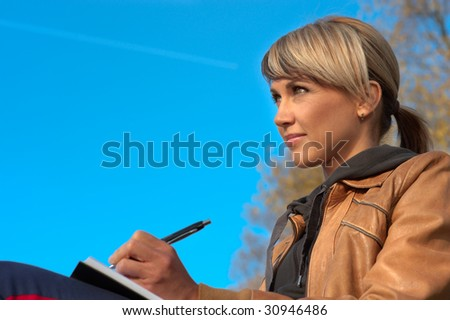 Woman writing in a park, sky on the background. - stock photo