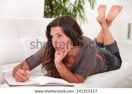 Woman writing in her diary - stock photo