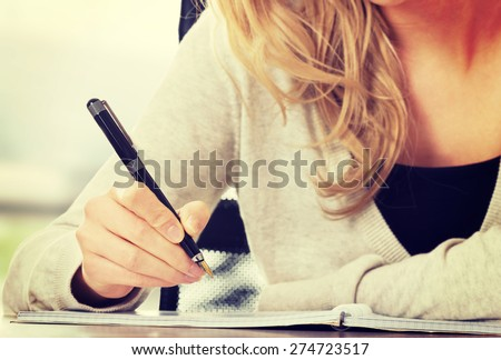 Woman writing in her notebook. - stock photo
