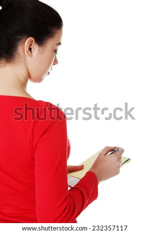 Woman writing notes and planning her schedule. - stock photo