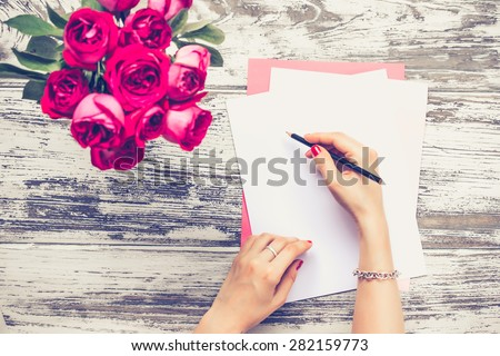 Woman writing on  blank paper sheets on old wooden table. Top view. Toned image - stock photo