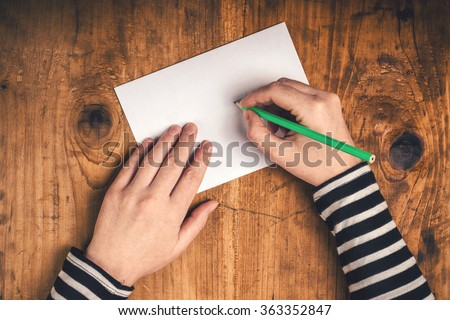 Woman writing recipient address on mailing envelope, female hands from above on office desk sending letter, top view, retro toned. - stock photo