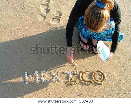 Woman writing with shells on beach - stock photo