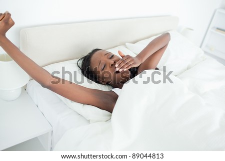 Woman yawning and stretching her arms in her bedroom - stock photo