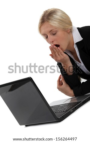 Woman yawning in front of computer - stock photo