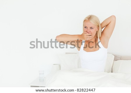 Woman yawning on her bed looking away from the camera - stock photo