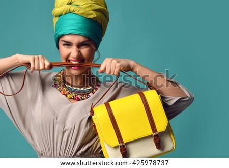 Woman yelling screaming and eating belt of hand hold stylish fashion yellow leather bag handbag isolated on blue mint background - stock photo
