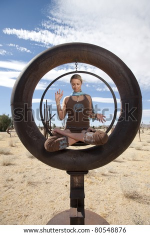 Woman yogi sitting in lotus pose with her hands in a spiritual mudra meditating inside of a large rusted steel circle . - stock photo