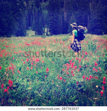 Woman young backpacking in wildflowers Instagram Style - stock photo
