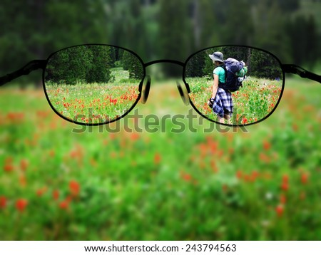 Woman young backpacking in wildflowers taking photograph blurred with glasses - stock photo