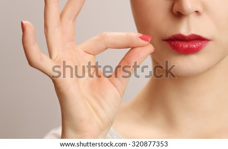 Woman zipping her mouth shut - keeping quiet concept - stock photo