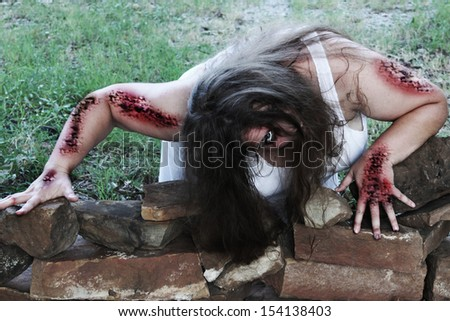 Woman zombie crawls out toward her victim - stock photo