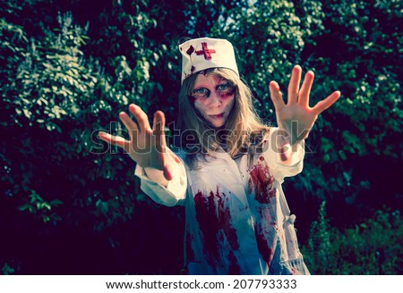 Woman zombie walking dead outdoors. Dark lighting. Color was changed to emphasize the atmosphere of horror. - stock photo