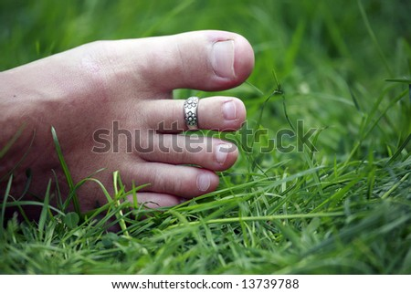 womanish foot with a decoration on the green grass - stock photo