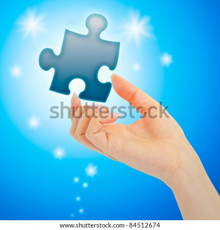 Womanish hand with a blue shining piece of puzzle on blue background - stock photo