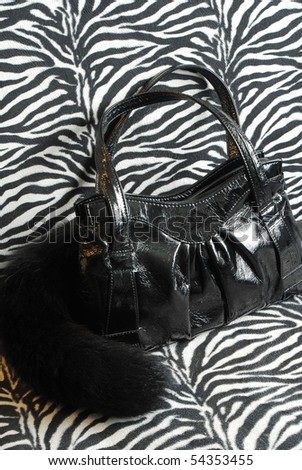 womans black bag and zebra texture - stock photo