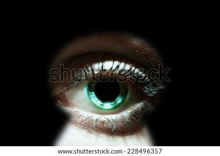 Womans eye peeking through a keyhole concept for curiosity, stalker, surveillance and security - stock photo