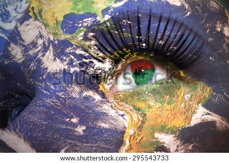 womans face with planet Earth texture and madagascar flag inside the eye. Elements of this image furnished by NASA. - stock photo