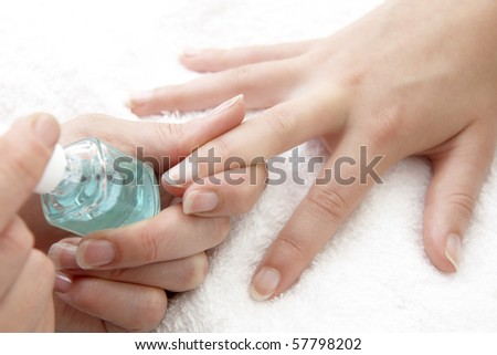 womans finger nails having clear varnish applied on white towel - stock photo