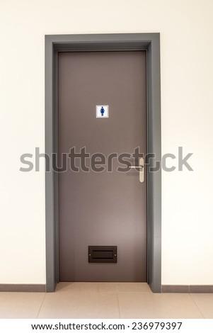 Womans restroom in an public building in Brown door. - stock photo