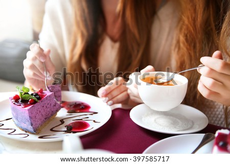 Womans with tasty cheesecake and cup of tea in cafe or restaurant  - stock photo