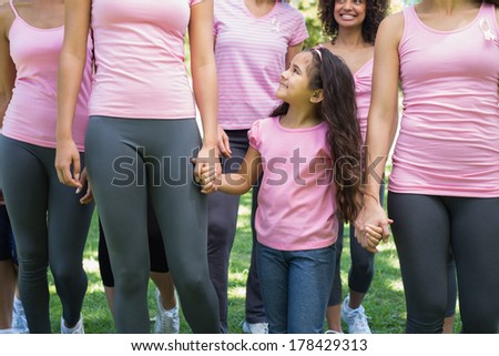 Women and girl participating in breast cancer awareness at park - stock photo
