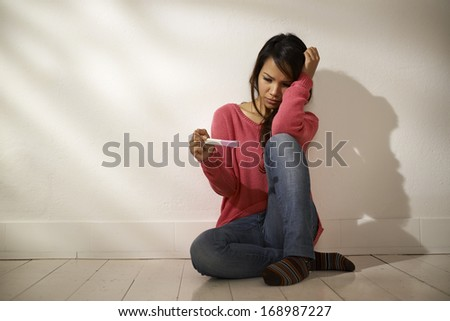 Women and health, anxious Asian girl looking at pregnancy test kit, sitting on ground at home - stock photo