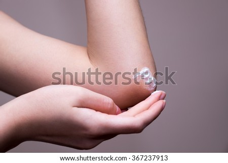 Women applying cream on elbow photo . women cream on elbow.Close-up of a woman takes care of his elbow using cosmetic cream. asia women applying his elbow with arm. women arm applying cream on elbow. - stock photo