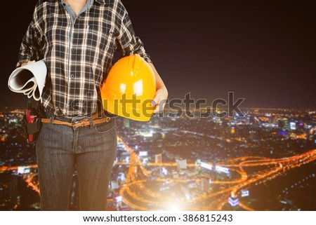 women architect in protective safety equipment goggles hard hat and blueprints working at high building construction site against urban scene balcony over looking city dusky before rain falling - stock photo