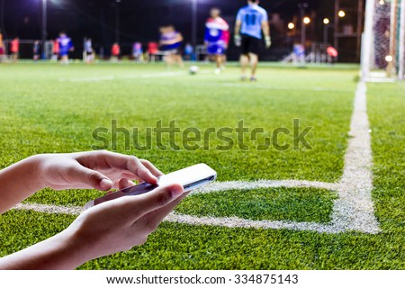Women are using smart phone on the football field . - stock photo